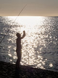 Man with a fishing rod at the sea in Corsica. On a summer evening Royalty Free Stock Photos