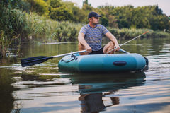 Man fishing from the rubber boat on the pond Stock Images