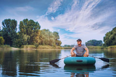 Man fishing from the rubber boat on the pond. Young man fishing from the rubber boat on the pond Stock Photo