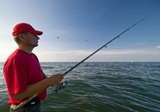 Man fishing at sea. A man fishing at sea (ocean) with a fishing rod Royalty Free Stock Image
