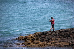 Man fishing in the sea stones Royalty Free Stock Images