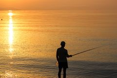 Man Fishing in the Sea at Sunrise Stock Images