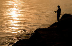 Man fishing at sea Stock Images