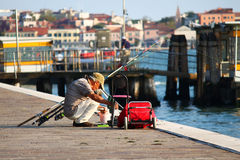 Man fishing from seafront near docks in Venice. This man is fishing with his longline rods from the seafront of Venice, near the docks Stock Images