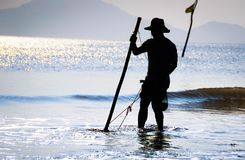 Man Fishing on Shallow Waters of the Beach Against the Light Photo during Daytime Royalty Free Stock Photos