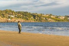 Man Fishing at Shore of Beach Royalty Free Stock Photo