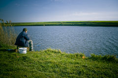 Man fishing on shore of lake. A view of a man sitting on the shore of a lake, fishing on a bright, sunny spring day Stock Photo