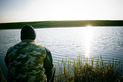 Man fishing on shore of lake. A view of the back of a man wearing a camouflaged jacket and knit hat, sitting and fishing on the shore of a lake late in the day Royalty Free Stock Photo