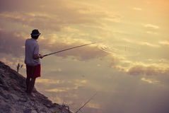 Man fishing in the sky reflection Stock Images