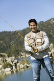 Man Fishing On A Sunny Day. Portrait of happy Hispanic mature man fishing on a sunny day Royalty Free Stock Images