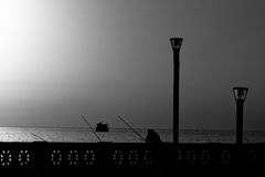 Man fishing at sunrise in B/W Stock Image