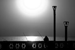 Man fishing at sunrise in B/W w/orange filter Royalty Free Stock Images