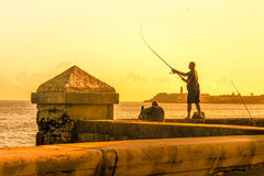 Man fishing during a sunset in Havana. Man fishing at the Malecon seawall during a sunset in Havana Stock Photography