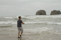 Man fishing in the surf on Rockaway beach. Oregon near twin Rocks Royalty Free Stock Photo
