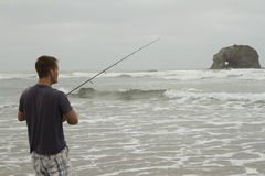 Man fishing in the surf on Rockaway beach. Oregon near twin Rocks Royalty Free Stock Image