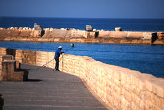 A man fishing in Tel Aviv - Israel. Man fishes on the coast of Tel Aviv - Israel Royalty Free Stock Photography