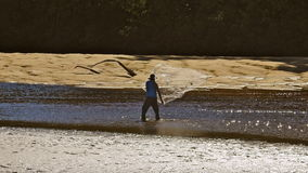 Man fishing throwing cast net in river water near bank Royalty Free Stock Image