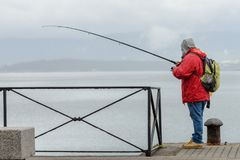 Man on a fishing trip on a pier with a dog. Image of man on a fishing trip on a pier Royalty Free Stock Photos