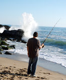 Man fishing and whaching wave. Man alone fishing on beach Royalty Free Stock Photo