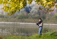 Man fishing. Young man fishing on the river in fall time Stock Images