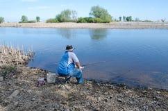 Man fiskesammanträde på en stol på flodbanken arkivfoton