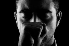 Man with fist and eyes closed. Portrait of a man with fist and eyes closed on black background Stock Images