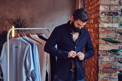 A man fit on fashionable shirts. Attractive bearded tattooed male fit on fashionable shirts in a store changing room Royalty Free Stock Images