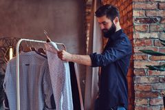 A man fit on fashionable shirts. Attractive bearded tattooed male fit on fashionable shirts in a store changing room Stock Images
