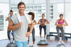 Man with fit people performing step aerobics exercise Royalty Free Stock Photos