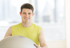 Man With Fitness Ball Smiling In Gym Stock Photography