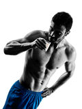 Man fitness exercises drinking milk silhouette. One caucasian man exercising fitness exercises drinking milk in studio silhouette isolated on white background Royalty Free Stock Photography