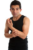 Man, fitness instructor, builder nursing sore arm royalty free stock image