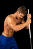 Man fitness no shirt on black pole look down Stock Photos