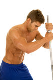 Man fitness no shirt on lean on poll look down Royalty Free Stock Photo