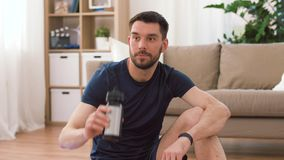 Man with fitness tracker drinking water at home. Sport, technology and healthy lifestyle concept - tired man with fitness tracker drinking water after training stock footage
