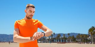 Man with fitness tracker training outdoors. Sport and healthy lifestyle concept - man with fitness tracker training outdoors royalty free stock images