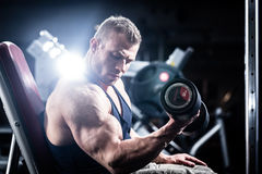 Man at fitness training with dumbbells in gym Stock Photos