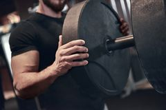 Man fitness. Young strong man during training in the gym stock photo