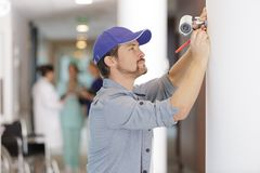 Man fitting cctv in hospital. Man fitting a cctv in hospital stock photo