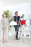 Man fitting ceiling light Stock Photography