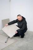Man fitting floor tiles royalty free stock image