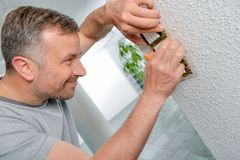 Man fitting light switches to wall stock image