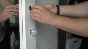 Man fitting a low energy CFL light bulb to replace an old-fashioned tungsten incandescent light bulb.  stock video footage