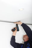 Man Fitting Metal Track To Ceiling Royalty Free Stock Image