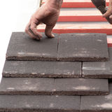 Man fitting roof tiles in rows Stock Photo
