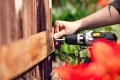 Man fixes a board to a wooden wall Stock Images