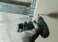 Man fixes the drywall. To metal frame using screws Royalty Free Stock Photo
