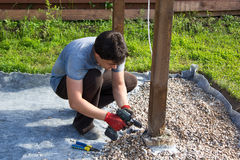 Man fixes electrical cord on a wooden post Stock Image