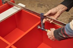 A man fixes the furniture with a clamp to dry the glue royalty free stock photos