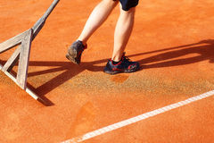 Man fixes the lines on tennis courts. Orange color background. Stock Images